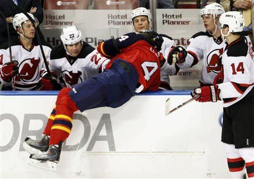 Florida Panthers defenseman Keaton Ellerby (4) is slammed into the New Jersey Devils bench by left wing Ilya Kovalchuk during the second period of an NHL hockey game, Tuesday, Dec. 13, 2011, in Sunrise, Fla. (AP Photo/Wilfredo Lee)