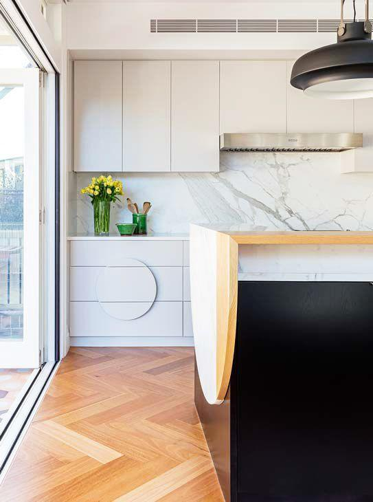 <p>A folded effect over the edge of the multi-hued island in this Arent & Pyke kitchen feels fresh and fun while keeping the room understated. The circle motif repeats in the pendant light and as a unique custom handle pull on the cabinets. <br></p>