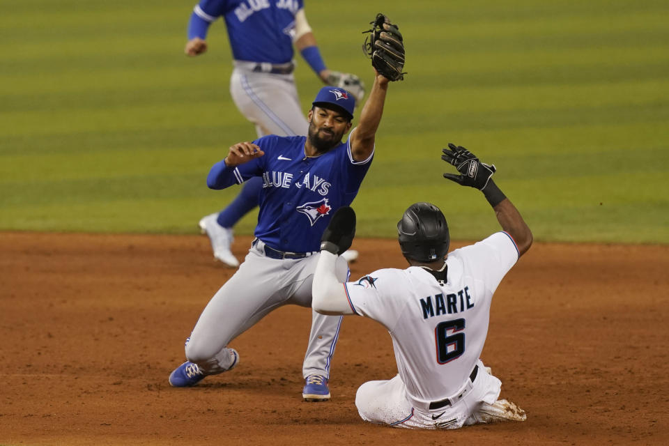 Toronto Blue Jays shortstop Marcus Semien, left, catches the ball as Miami Marlins' Starling Marte, right, is late stealing second base during the ninth inning of a baseball game, Tuesday, June 22, 2021, in Miami. The Blue Jays defeated the Marlins 2-1.(AP Photo/Marta Lavandier)