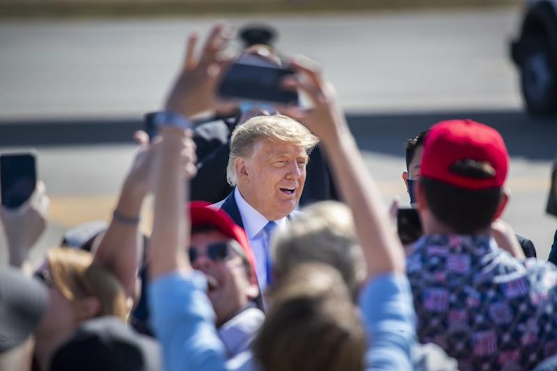 SANTA ANA, CA - OCTOBER 18: President Donald Trump greets supporters as he arrives on Air Force One at John Wayne Airport on Sunday, Oct. 18, 2020 in Santa Ana, where he will be attending a fundraiser at the home of Palmer Luckey on Lido Island in Newport Beach. (Allen J. Schaben / Los Angeles Times)