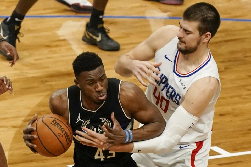 LA Clippers' Ivica Zubac tries to stop Milwaukee Bucks' Thanasis Antetokounmpo during the second half of an NBA basketball game Sunday, Feb. 28, 2021, in Milwaukee. (AP Photo/Morry Gash)