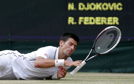 Novak Djokovic of Serbia slips during his men's singles final tennis match against Roger Federer of Switzerland at the Wimbledon Tennis Championships, in London July 6, 2014. REUTERS/Stefan Wermuth