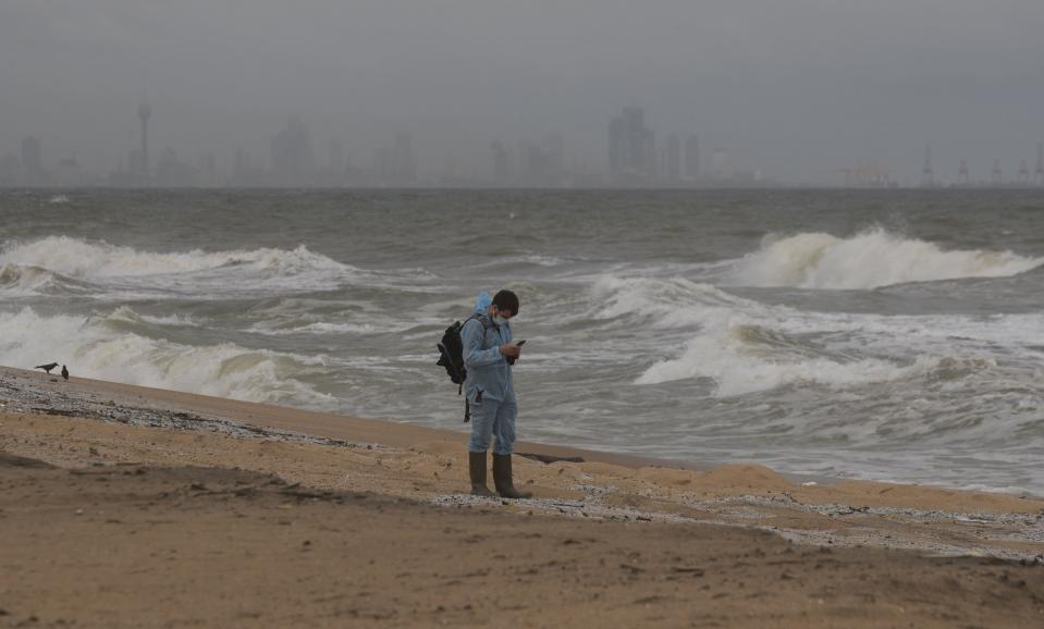 An unidentified foreign investigator inspects debris washed ashore on the beach from the fire-damaged container ship MV X-Press Pearl in Kapungoda, on the out skirts of Colombo, Sri Lanka, Friday, June 4, 2021. Authorities were trying to head off a potential environmental disaster as the Singapore flagged ship that had been carrying chemicals was sinking off of the country's main port. (AP Photo/Eranga Jayawardena)