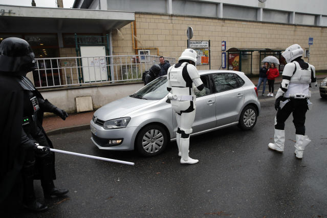 In this Sunday, Feb. 10, 2019, photo, men dressed up as Stormtroopers joke as they control a car during the national lightsabers tournament in Beaumont-sur-Oise, north of Paris. In France, lightsaber fighting is an official sport, recognized as such by the French Fencing Federation. The sport's practitioners, many but not all of the fans of 'Stars Wars,' have had to build the discipline's competition rules almost from scratch. (AP Photo/Christophe Ena)