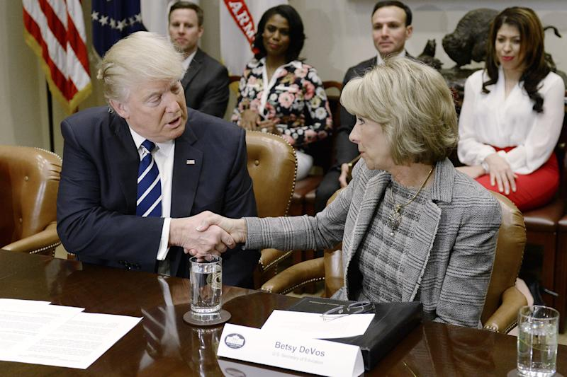 President Donald Trump shakes hands with Betsy DeVos during a parent-teacher conference listening session inside the Roosevelt Room of the White House on Tuesday, Feb. 14, 2017. (Bloomberg via Getty Images)