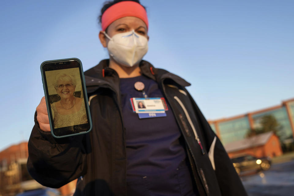 Nurse Jessica Franz, shows a photo of her mother-in-law, Elaine Franz, outside Olathe Medical Center after working the graveyard shift Thursday, Nov. 26, 2020, in Olathe, Kan. Elaine Franz died Nov. 10, one day before her 78th birthday, after contracting COVID-19. (AP Photo/Charlie Riedel)