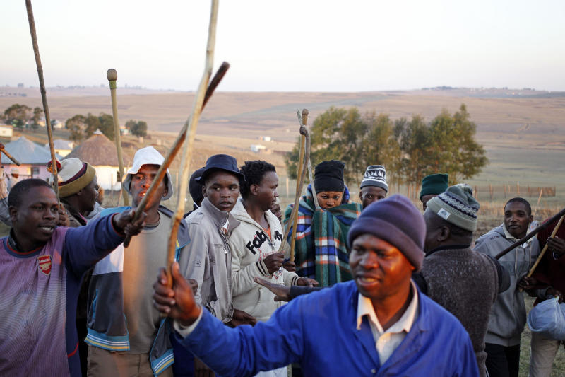 In this photo taken on Thursday, July 11, 2013, men dance around a boy, fourth from right in rear, covered with a blanket, after he completed his initiation ceremony near Qunu, South Africa. Initiation ceremonies in South Africa's Eastern Cape province have led to the deaths of more than 60 young men since May and the hospitalization of hundreds, sparking concern from government and health officials about the lack of regulation of a national tradition that determines when a boy becomes a man. (AP Photo/Schalk van Zuydam)