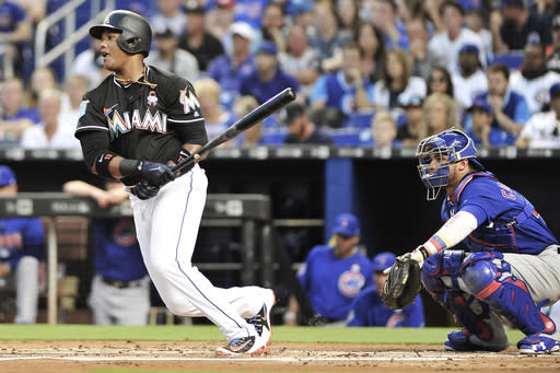 Miami Marlins' Starlin Castro, left, singles to center in the first inning of a baseball game against the Chicago Cubs in Miami, Friday, March 30, 2018. (AP Photo/Gaston De Cardenas)