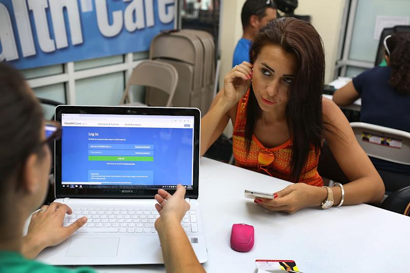 Alina Nurieva, right, picks an insurance plan available in the third year of the Affordable Care Act at a store set up in Miami's Mall of the Americas on Nov. 2, 2015. (Joe Raedle via Getty Images)