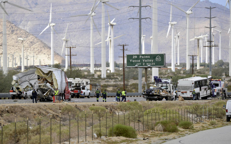 FILE - In this Oct. 23, 2016, file photo, tow truck drivers prepare to haul away a tour bus that crashed with a semi-truck on Interstate 10, west of the Indian Canyon Drive off-ramp, in Desert Hot Springs, near Palm Springs, Calif.  Officials say Bruce Guilford, a trucker who fell asleep behind the wheel was sentenced, Friday, Aug. 30, 2019,  to four years in state prison after he pleaded guilty to causing a tour bus crash on a Southern California freeway that killed 13 people in 2016. (AP Photo/Rodrigo Pena, File)