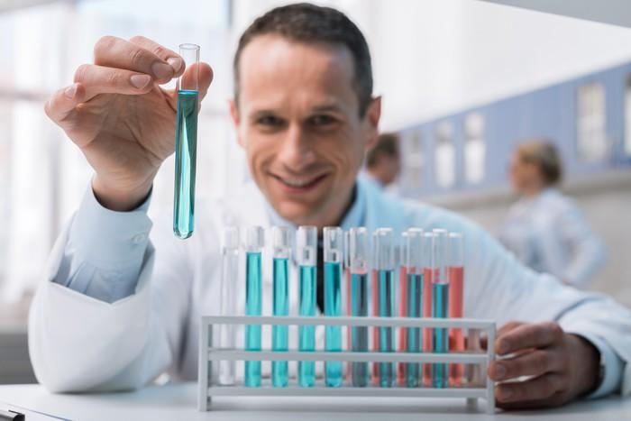 A man in a lab coat smiling and holding test tube with a rack of test tubes in front of him.