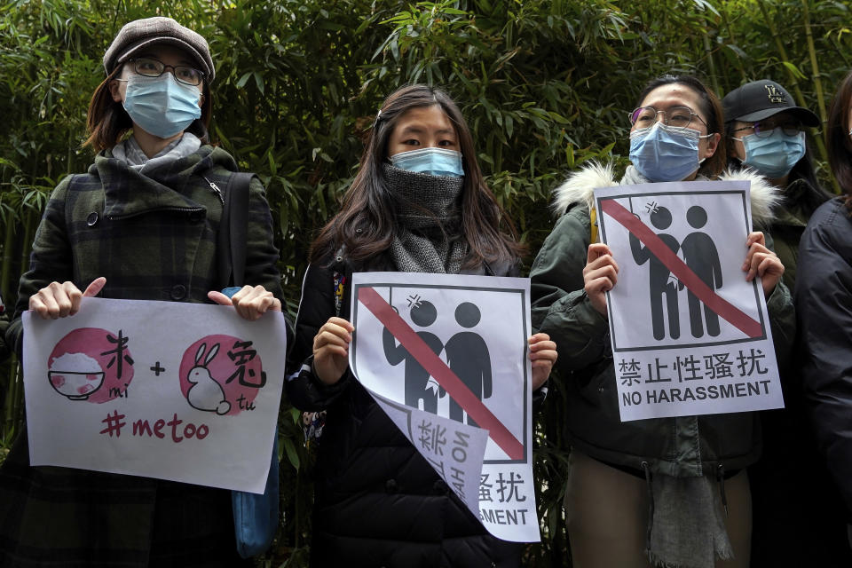 Supporters of Zhou Xiaoxuan hold banners as they wait for Zhou outside at a courthouse where she is appearing in a sexual harassment case in Beijing, Wednesday, Dec. 2, 2020. A high profile case of sexual harassment in China's #MeToo movement involving a well-known Chinese state TV host will be start on Wednesday in the capital city after pending for more than two years. (AP Photo/Andy Wong)