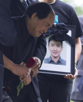 Dirang Lin, father of slain student Jun Lin prepares to lay a rose at his son's gravesite during funeral services in Montreal, July 26, 2012.
