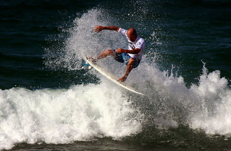 FILE PHOTO: Eleven-time world surfing champion Slater of the US rides a wave during a promotional event at Sydney's Manly Beach