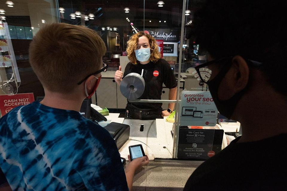 <p>Movie goers buy tickets at the AMC Highlands Ranch 24 on August 20 in Highlands Ranch, Colorado.</p>