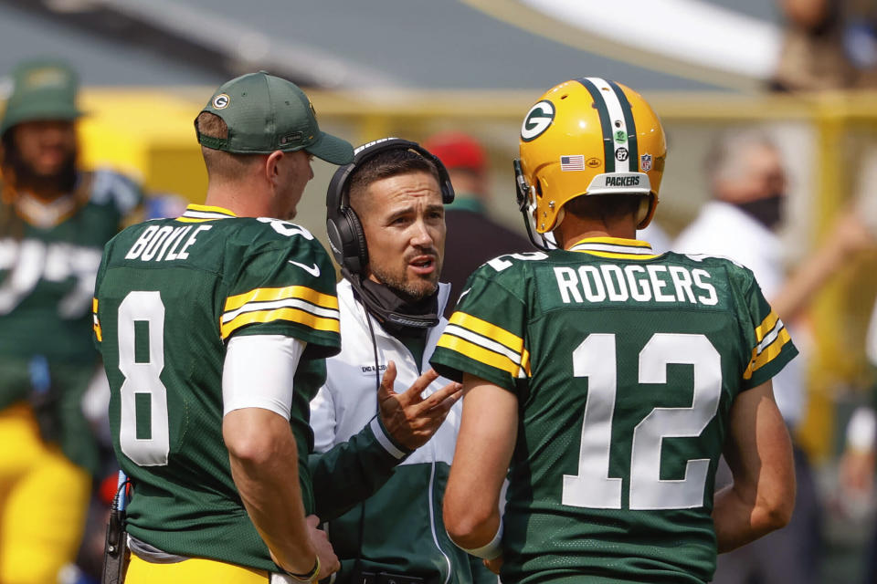 Green Bay Packers head coach Matt LaFleur speaks to Aaron Rodgers (12) and Tim Boyle (8) during a timeout of an NFL football game against the Detroit Lions Sunday, Sept. 20, 2020, in Green Bay, Wis. The most recognizable trend in hiring NFL head coaches has been to target young, innovative offensive teachers with a track record of developing quarterbacks. (AP Photo/Jeffrey Phelps)