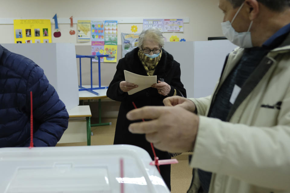 A woman prepares her ballot for the local elections at a polling station in Mostar, Bosnia, Sunday, Dec. 20, 2020. Divided between Muslim Bosniaks and Catholic Croats, who fought fiercely for control over the city during the 1990s conflict, Mostar has not held a local poll since 2008, when Bosnia's constitutional court declared its election rules to be discriminatory and ordered that they be changed. (AP Photo/Kemal Softic)