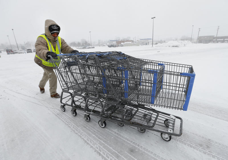 Anthony Avery pushes grocery carts during a snow storm in Roseville, Mich., Wednesday, March 12, 2014. The storm will likely move the Detroit area close to the seasonal snow total of 93.6 inches set in 1880-1881, according to the National Weather Service. (AP Photo/Paul Sancya)