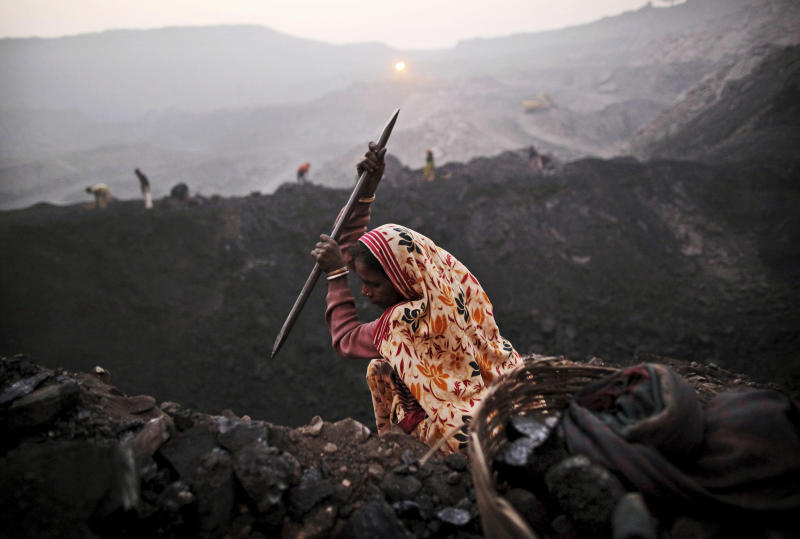 FILE - In this Jan. 7, 2011 file photo, a laborer chips away at a seam of coal as she scavenges at an open-cast mine in the village of Bokapahari in the eastern Indian state of Jharkhand where a community of coal scavengers live and work. India's Parliament is in an uproar over a report by government auditors that the country lost nearly US$210 billion in revenue by selling off coalfields to private and state-run companies without competitive bidding. (AP Photo/Kevin Frayer, File)