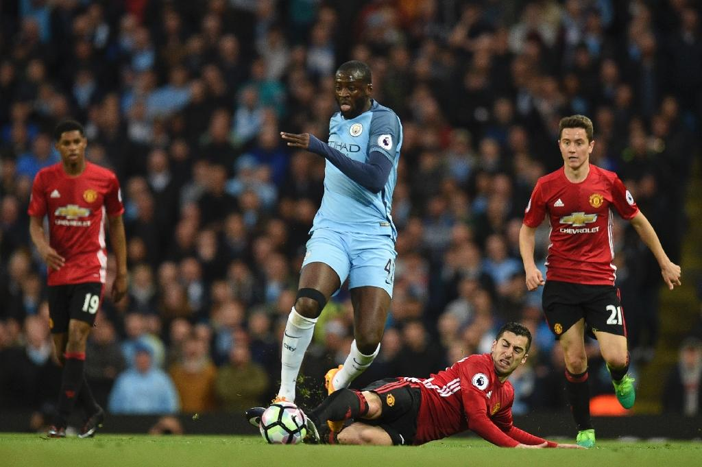 Manchester City's Yaya Toure (CL) vies with Manchester United's Henrikh Mkhitaryan during their English Premier League football match at the Etihad Stadium in Manchester, north west England, on April 27, 2017 (AFP Photo/Oli SCARFF                          )