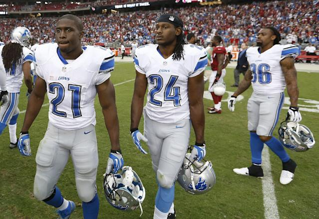Detroit Lions' Reggie Bush (21), DeJon Gomes (24) and Jonte Green (36) walk off the field after a loss against the Arizona Cardinals in an NFL football game on Sunday, Sept. 15, 2013, in Glendale, Ariz. The Cardinals defeated the Lions 25-21. (AP Photo/Ross D. Franklin)
