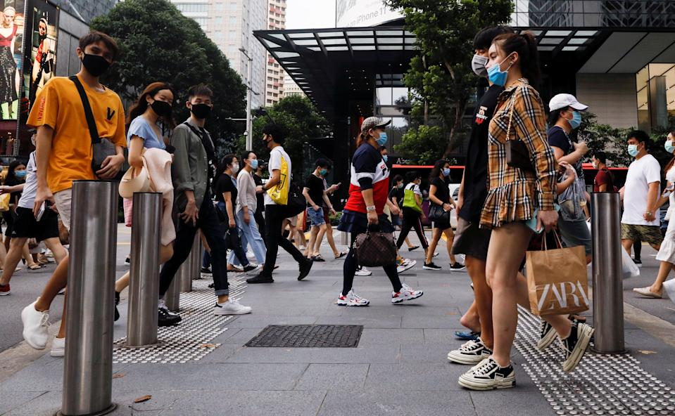 People cross a street at the shopping district of Orchard Road as the city state reopens the economy, amid the coronavirus disease (COVID-19) outbreak, in Singapore June 19, 2020.  REUTERS/Edgar Su