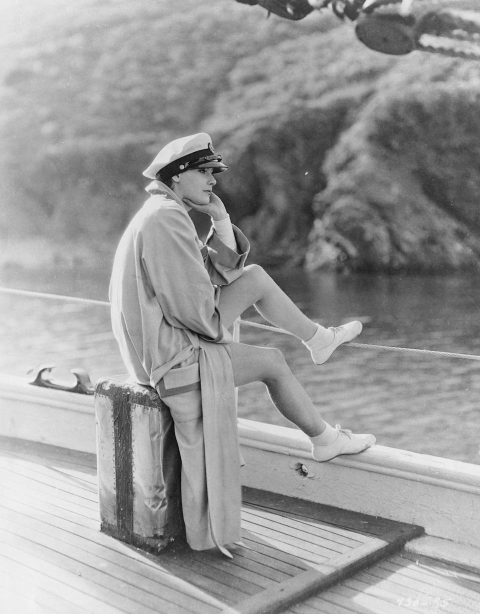 <p>Greta Garbo looks out on the horizon while relaxin on the deck of a boat. The film star is dressed casually in an oversized trench coat and sailor's cap. </p>