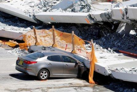 A damaged car is seen partially trapped as workers remove debris from a collapsed pedestrian bridge at Florida International University in Miami, Florida, U.S., March 16, 2018. REUTERS/Joe Skipper