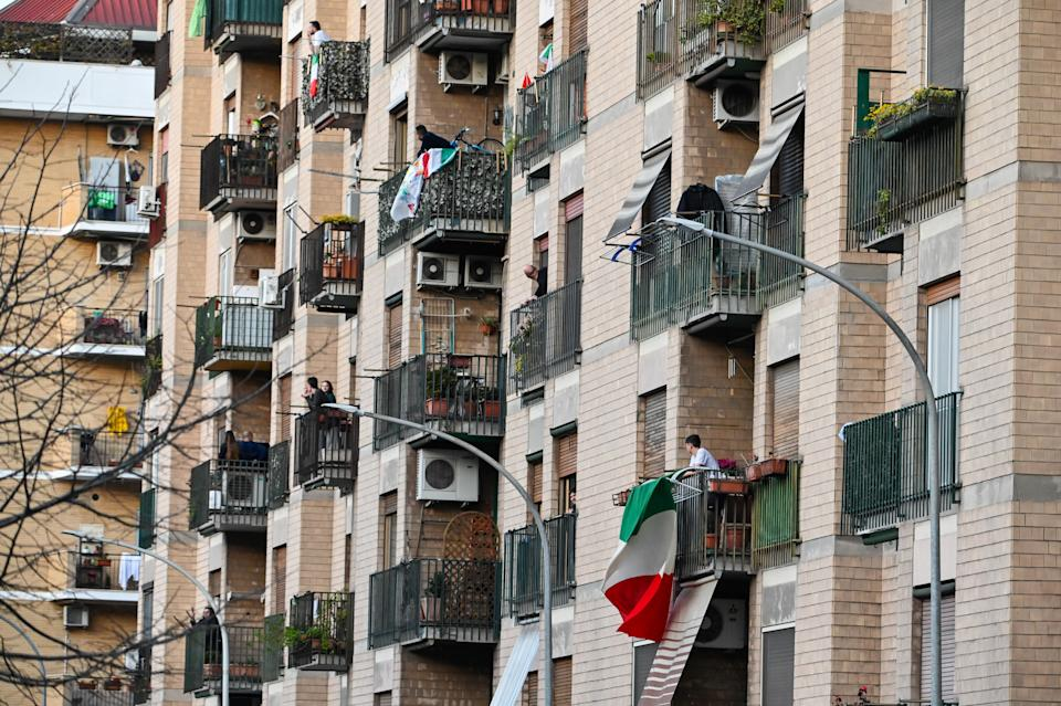 """People wave and clap their hands next to a Italian flags, during a flash mob """"Una canzone per l'Italia"""" (A song for Italy) at Magliana district in Rome on March 15, 2020. - Italy reacts with the solidarity of flash mobs circulating on social media to make people """"gather"""" on balconies at certain hours, to play music or to get a round of applause. Italy on Sunday recorded 368 new deaths from the novel coronavirus, its highest one-day increase to date, taking the total to 1,809, the most outside China, official data showed. The number of infections has reached 24,747, a count released to the media by Italy's civil protection service said. The northern Lombardy region around Milan remained the European epicentre of the pandemic, officially reporting 1,218 deaths, or 67 percent of the Italian total. (Photo by Andreas SOLARO / AFP) (Photo by ANDREAS SOLARO/AFP via Getty Images)"""