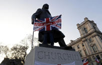 """FILE - In this file photo dated Friday, March 29, 2019, a pro-Brexit demonstrator holds a British flag with the words """"Leave Means Leave"""" in front of the Winston Churchill statue in London. The Brexit decision to split from the European Union was fuelled by a sense that the U.K. is fundamentally separate from its continental neighbours, but both sides of the Brexit debate conjure up strong historical concepts for this sceptered isle.(AP Photo/ Kirsty Wigglesworth, FILE)"""