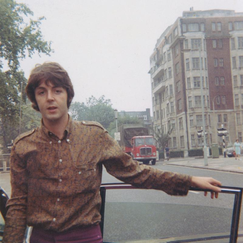 Portrait of Paul McCartney from The Beatles posed wearing a paisley shirt by a car door in a London street circa 1966.