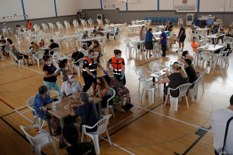 Evacuated residents arrive at a sports center due to a wildfire on Sierra Bermeja mountain