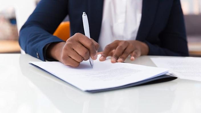 Businesswoman signing contract. African American business woman sitting at table in office, holding pen and writing in document. Legal expertise concept