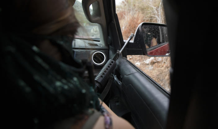 """An armed woman known as """"La Guera,"""" who says she is a member of a female-led, self-defense group, patrols the edge of their town of El Terrero, where it shares a border with the town of Aguililla, in Michoacan state, Mexico, Thursday, Jan. 14, 2021. The vigilantes bitterly deny allegations they're part of a criminal gang, though they clearly see the Jalisco cartel as their foe. They say they would be more than happy for police and soldiers to come in and do their jobs. (AP Photo/Armando Solis)"""