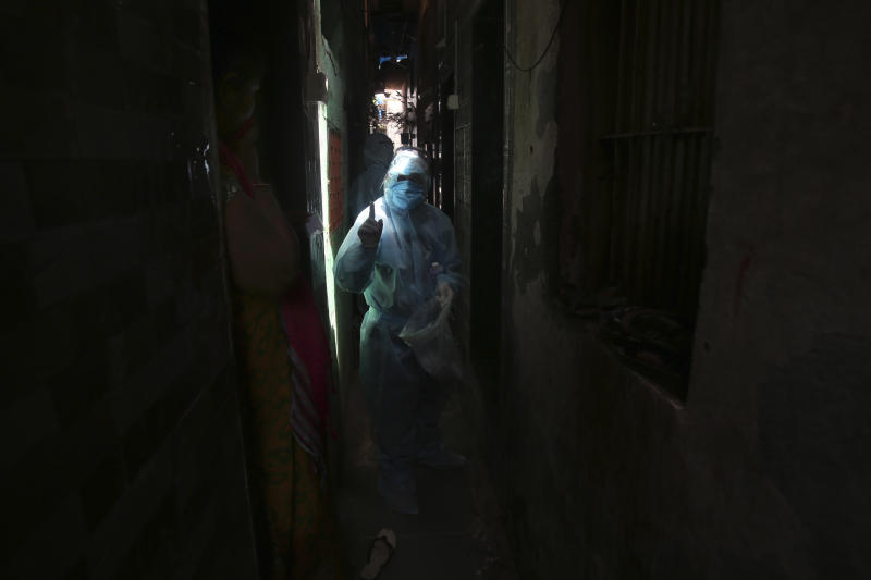 An Indian health worker wearing personal protective equipment speaks with a woman during a check up camp at a slum in Mumbai, India, Wednesday, June 17, 2020. India is the fourth hardest-hit country by the COVID-19 pandemic in the world after the U.S., Russia and Brazil. (AP Photo/Rafiq Maqbool)