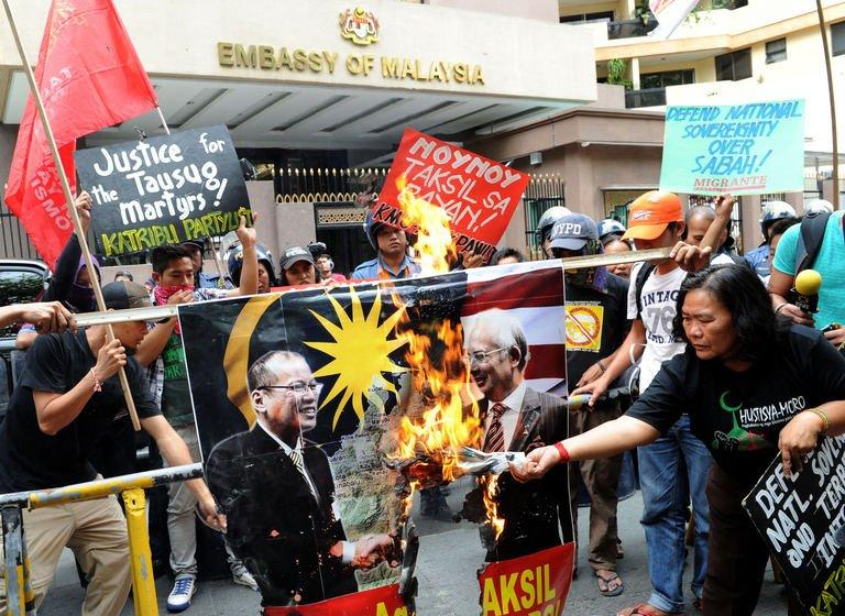 Protesters burn portraits of Philippine and Malaysian leaders outside the Malaysian embassy in Manila on March 5, 2013