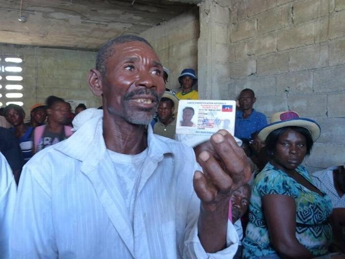 In this file photo, a cholera victim holds up his Haitian national identification card as he discussed the psychological and physical scars of the waterborne disease. He is among scores of cholera victims who gather regularly in Haiti's Cité Soleil slum to get updates on their plea for individual compensation from the United Nations.