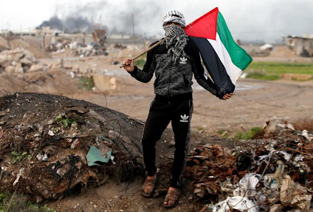 """<p>A protester holds a Palestinian flag as he poses for a photograph at the scene of clashes with Israeli troops near the border with Israel, east of Gaza City, Jan. 19, 2018. """"The battle between us and the Israeli occupation has been ongoing for decades. We will continue to protest and resist as long as there is one Israeli occupier on our land. Trump and anyone else in this world will not be able to control our anger,"""" he said. (Photo: Mohammed Salem/Reuters) </p>"""