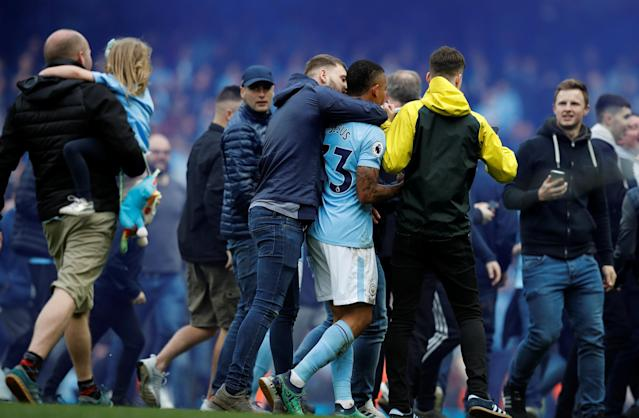 "Soccer Football - Premier League - Manchester City v Swansea City - Etihad Stadium, Manchester, Britain - April 22, 2018 Fans celebrate with Manchester City's Gabriel Jesus on the pitch after the match REUTERS/Phil Noble EDITORIAL USE ONLY. No use with unauthorized audio, video, data, fixture lists, club/league logos or ""live"" services. Online in-match use limited to 75 images, no video emulation. No use in betting, games or single club/league/player publications. Please contact your account representative for further details."