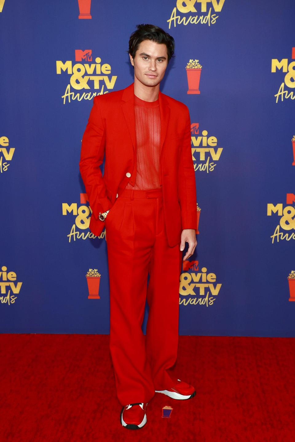 """In a sea of color, red appeared to be the <em>it</em> choice of the season. Matching with co-star and IRL girlfriend Madelyn, it only made sense that <a href=""""https://www.teenvogue.com/story/outer-banks-season-2-finished-filming?mbid=synd_yahoo_rss"""" rel=""""nofollow noopener"""" target=""""_blank"""" data-ylk=""""slk:Outer Banks"""" class=""""link rapid-noclick-resp""""><em>Outer Banks</em></a> actor Chase Stokes would show up head to toe in it. Styled by Avoyer Magnan, Chase wore a monochrome Fendi ensemble. They say red is a passionate color and the pair <em>did</em> share <a href=""""https://www.teenvogue.com/story/outer-banks-stars-chase-stokes-madelyn-cline-shared-kisses-mtv-movie-and-tv-awards-2021?mbid=synd_yahoo_rss"""" rel=""""nofollow noopener"""" target=""""_blank"""" data-ylk=""""slk:a passionate kiss on stage after winning the Best Kiss award"""" class=""""link rapid-noclick-resp"""">a passionate kiss on stage after winning the Best Kiss award</a>, after all!"""