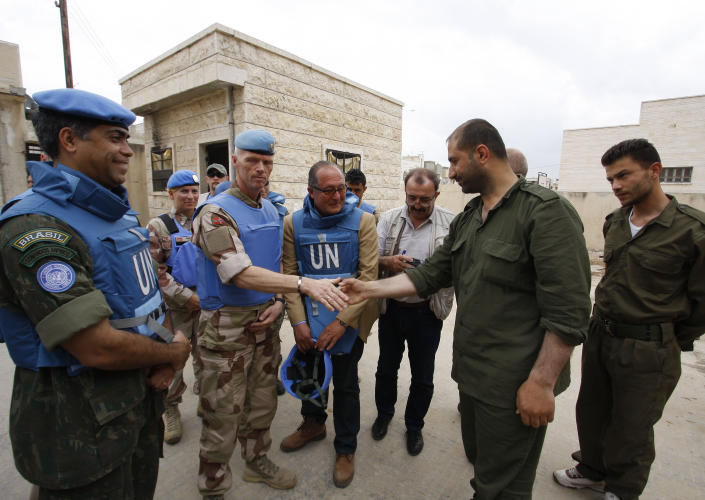 In this picture taken during a UN observer-organized tour, the head of the advance team of UN observers, Maj. Gen. Robert Mood, center left, shakes hands with a Syrian security officer during their visit to Hama city, central Syria, on Thursday, May 3, 2012. Syrian security forces stormed dorms at a northwestern university to break up anti-government protests there, killing at least four students and wounding several others with tear gas and live ammunition, activists and opposition groups said Thursday. (AP Photo/Muzaffar Salman)