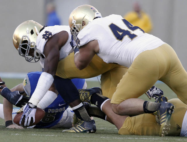 Notre Dame linebacker Jaylon Smith, front left, picks up a ball fumbled by Air Force quarterback Nate Romine, back left, as Notre Dame linebacker Carlo Calabrese, front right, covers in the third quarter of Notre Dame's 45-20 victory in an NCAA football game in Air Force Academy, Colo., Saturday, Oct. 26, 2013. (AP Photo/David Zalubowski)