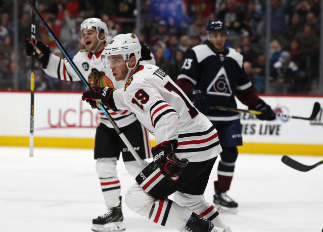 Chicago Blackhawks center Jonathan Toews, front, joins left wing Alex DeBrincat, back left, in celebrating after Patrick Kane scored in overtime, as Colorado Avalanche left wing Matt Nieto watches during an NHL hockey game Saturday, Dec. 29, 2018, in Denver. The Blackhawks won 3-2. (AP Photo/David Zalubowski)