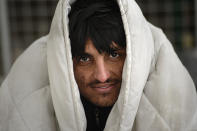 A migrant smiles while sitting covered in a blanket in a temporary shelter at the Lipa camp northwestern Bosnia, near the border with Croatia, Saturday, Dec. 26, 2020. Hundreds of migrants are stranded in a burnt-out squalid camp in Bosnia as heavy snow fell in the country and temperatures dropped during a winter spell of bad weather after fire earlier this week destroyed much of the camp near the town of Bihac that already was harshly criticized by international officials and aid groups as inadequate for housing refugees and migrants.(AP Photo/Kemal Softic)