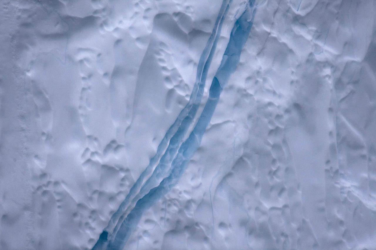 In this July 18, 2011 photo, a vein of highly-compacted blue ice runs along the surface of an iceberg shed from the Greenland ice sheet, near Ilulissat, Greenland. (AP Photo/Brennan Linsley)