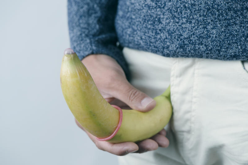 closeup of the a young caucasian man holding a banana with a pink condom in it in front of his crotch