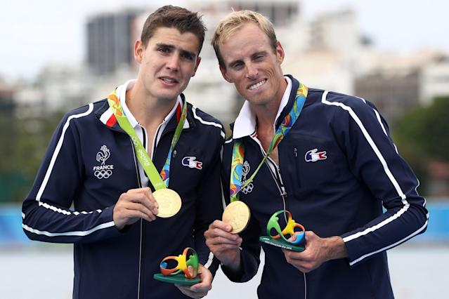 <p>Gold medalists Pierre Houin (L) and Jeremie Azou (R) of France celebrate on the podium at the medal ceremony for the Lightweight Men's Double Sculls on Day 7 of the Rio 2016 Olympic Games at Lagoa Stadium. (Getty) </p>