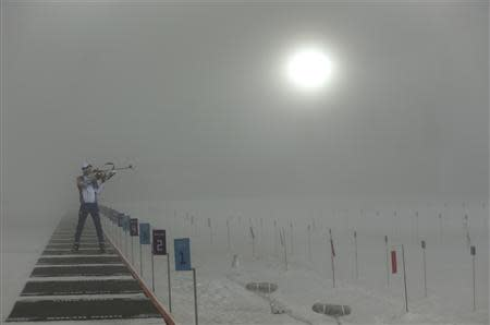 An athlete practices on the shooting range before men's biathlon 15km mass start event at Sochi 2014 Winter Olympics