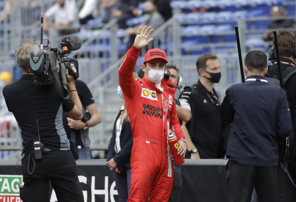 Ferrari driver Charles Leclerc of Monaco, center, waves after the qualifying session at the Monaco racetrack, in Monaco, Saturday, May 22, 2021. The Formula One race will take place on Sunday with Ferrari driver Charles Leclerc of Monaco in pole position. (AP Photo/Luca Bruno)