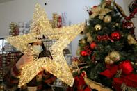 A Palestinian shop-owner arranges christmas decorations at her shop in the West Bank city of Bethlehem